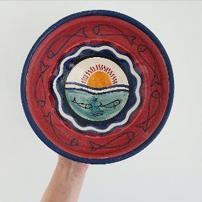 Stor skøn og håndmalet skål med fisk og solnedgang. Måler 26 cm i diameter og 10 cm I højden. I meget fin stand, lidt afskaldning på kanten og små krakkeleringer.
