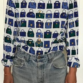 """Fin vintage skjorte med tasker på. Fra Lucia.  Mangler en knap øverst og to ved det ene ærme. Ekstra knap inde i blusen. Se billede.  Udover de manglende knapper, fejler skjorten intet og er i fin stand. Det er udelukkende de manglende knapper, der gør, at skjorten er i """"slidt"""" stand.  Hvis ærmerne foldes op, er der ikke brug for knapper."""