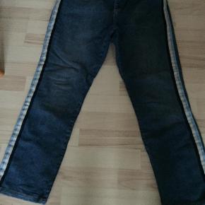Varetype: Jeans Farve: Denim  Flotte 3/4 lange jeans fra Ellos Str 48 i cotton og spandex . Bukserne har aldrig været brugt kun vasket. Bukserne har stribe ned langs siden i hvid marine og lyseblå . Fantastisk til foråret til en hvid bluse og et par lækre sneakers.