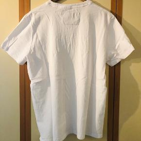 Frisk hvid T-shirt fra SuperDry med tryk for sælges da den aldrig er kommet i brug siden den blev købt ved SuperDry i Århus. T-shirten er fremstillet i meget kraftigt blødt stof hvilet gør den behagelig at bære.  Kom med et fair bud