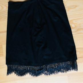 Sort velour agtig nederdel med søde blonder for neden. Lukkes med lynlås og knap bagpå