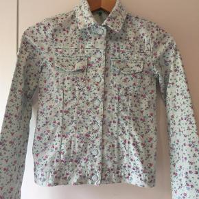 Rigtig sød blomstret cowboy jakke m trykknapper i elastisk jeansstof. Str 150 eller XL børn. Måler 50 i længden, ærmer 56-57, brystmål 78 cm.  Se andre annoncer.  Jakke Farve: Multi