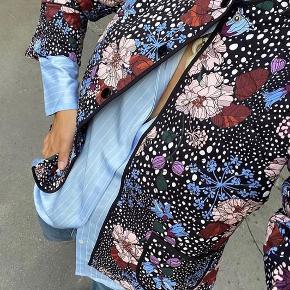 Blomstret quiltet overgangsjakke fra Dea Kudibal. Jakken er let foret med A-formede ærmer som puffer let ved skulderne. Jakken har fem knapper og to lommer foran.  Helt ny og med mærke på endnu Bud over 1700+