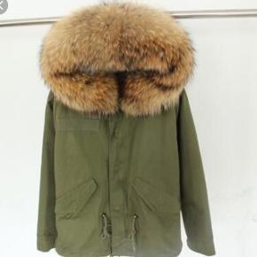 """Armygrøn, tætsiddende parkajakke med stor brun pelshætte. Hætten er af pels fra vaskebjørn. Foret er af rævepels. Jakkens fyld består af bomuld.  Lukkes med lynlås. Har lommer, der kan knappes. Kan snørres ind i taljen.  Jakken kan bruges både efterår/vinter/forår, da den er """"delt i to"""". Den inderste jakke (altså foret) kan altså tages ud, så den ikke er så varm.  Ellers er den meget varm, da den er tyk og beskrevet som """"broadcloth"""".  Np 3500 - er åben for realistiske bud"""