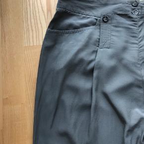 Lækre bukser i skinnende kvalitet og med lækre detaljer. Knaplukning foran Lommer i siderne