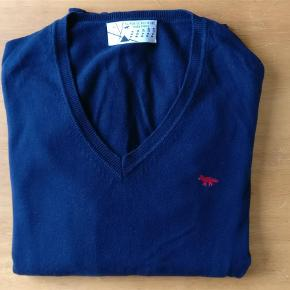 Varetype: mand trøje Farve: blå  Lækker trøje fra Maison Kitsune produceret i italien og i ren bomuld. Blusen er i fin condition eneste mangel er et syninger som er løbet i kanten. ses på billede 2
