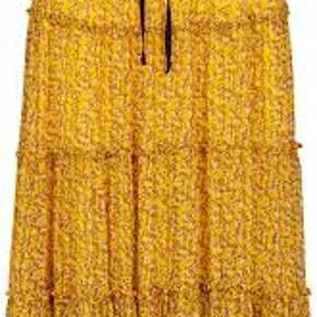 Smuk nederdel fra Second Female. Skirtet har skønt blomsterprint på en mørkegul baggrund. Branch skirt har bindebånd og elastik i livet, pasformen er løs og nederdelen er skåret i flere lag adskilt af flæsekant, der giver liv og fylde til nederdelen. Skirtet har midilængde og går perfekt til både bare ben og en strømpe. Stoffet er transparent og der er fastsyet underskørt.  100% viscose