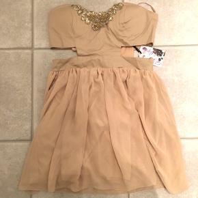 Virkelig sød beige kjole fra Elise Ryan. Aldrig brugt, prismærke sidder i. Ny pris: 150 kr. Pris nu: 75 kr.  Størrelse: UK 12 (hvilket svare til str. 40) men det passer på ingen måde. Den er smal i taljen til en str. 36.  Kan hentes på Amager - ellers sender jeg med DAO (køber betaler fragt)