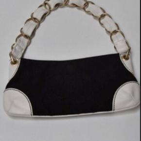 Super flot, elegant og tidsløs taske fra Chanel.   Den er lavet af sort Canvas og hvidt skind.   Den er kun anvendt få gange så er med minimale brugsspor.   Mål: 23 x 13cm  Den er naturligvis ægte med serienr.   Original dustbag følger med.   OBS billederne er af den pågældende taske☀️