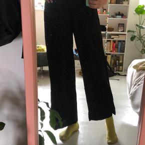 Løse sorte bukser med elastik i taljen. Der er to lommer foran. Brugt højest 3 gange.