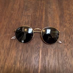 Medfølger original etui i brun læder samt brilleklud. Fragt er inkluderet i prisen.  Model: RB3447 Round Metal 001 5002