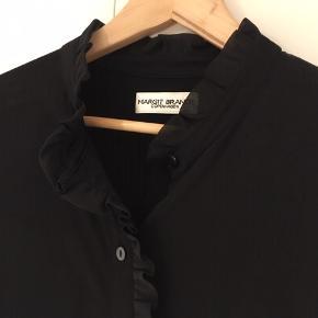 Skjorte, MARGIT BRANDT, str. 42, str. L  Model: MISY SHIRT 3129. 100% i orden, anvendt ganske få gange.  Feminin skjorte bluse fra MARGIT BRANDT i en høj halsudskæring med flæser samt flæse detalje langs knappelukningen foran. Skjorte blusen har transparente ærmer med bred manchet samt logo brodering. venstre side. 100% viskose. (kr. 799,-)