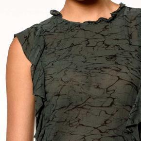 #30dayssellout Str. 2 svarende til S/M Hola Toppen  fra Bellerose har en tidløs elegance. Den delikate, vintageinspirerede form  udgør et moderne, abstrakt sort tryk på en baggrund af skovgrøn. Den er let og halv-gennemsigtig, med en blød flæse ved halsen samt på ryg og foran.  Lukkes ved bånd i nakken. -  Materiale: 100% viskose – den er ny – stadig med pristag – købt for 159 euro (1200 kr) – sælges for 350 kr