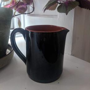 🌷 Skøn robust retro keramik kande i sort med brændt farve indvendigt. Kan bruges til alt fra køkkenredskaber, blomster eller bestik. Fejler ingenting udover en lille mini flig ved kanten, som man absolut ikke ligger mærke til. Måler 13 cm i højden.  Vase - mælkekande - bestikholder - vintage ✨   💚 Bytter ikke og prisen er fast!   🌍 Afhentes på Nørrebro  💌 Kan sendes for 33 kr med DAO