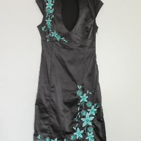 100 % NY:  Såå flot sort kjole m grønt broderi og med en 45 cm høj slidse i venstre side.Materialet er 92 % polyester + 8 % elastan.  Brystvidde: 45 cm -max 51 cm x 2 ( pga elastan) Livvidde: 34 cm - max 39 cm x 2 (pga elastan) Hoftevidde: 44 cm - max 51 cm x 2 (pga elastan) Længde: 99 cm  Bytter ikke med andre ting, og prisen er fast