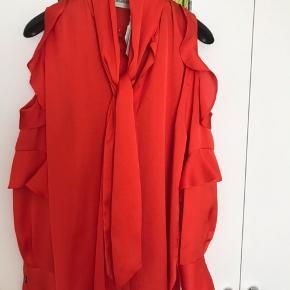 Skinnende skjorte med kig til skulderen fra By Malene Birger. Den er detaljeret med et aftageligt halstørklæde og flæser der går ned langs begge ærmer.  Materialer: 100% polyester Str. 34 Ny med prismærke 1.799kr Din pris 3.99kr