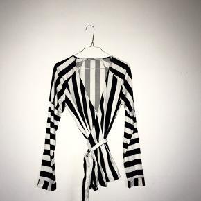 Stribet sort/hvid wrap-bluse. Aldrig brugt.