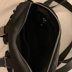 Taske fra Núnoo, med et stort rum som indeholder et mindre. Den har også et mellem rum på forsiden og to små. Tasken har to rem som kan justeres og tages af og på.