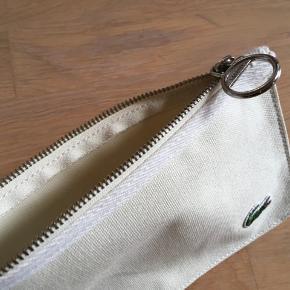 Aldrig brugt, tidløs, god kvalitet, praktisk skuldertaske /sportstaske / shopper / strandtaske og mm. med lille toilettaske / pung som kan tages af😊 Højde 30 cm  Brede 39 cm Dybde 13 cm inderside er tasken vandafvisende og indeholder et rum som lukkes med lynlås  Lacoste Bluse, Puma sneakers str. 38 følger ikke med, men kan tilkøbes.  Hvis du er interreseret i den flotte Lacoste skuldertaske sender jeg gerne nøjagtige mål og flere fotos.   Oprydningssalg, tages ikke retur, pris plus fragt