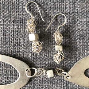 Sølvsmykker af eget design.  Matchende halskæde og øreringe.  Sterling sølv. Kun ørekrogene er stemplede (S925), da smykkerne er håndlavede. Selv de små terninger, er lavet / skåret / loddet i hånden. Ringene er selvfølgelig også håndlavede.  Kan bruges både pudset op eller oxyderede.  Halskæden er ca. 49 cm i længden men den kan lukkes variabelt. Øreringene er ca. 3,5 cm i højden.  Jeg får desværre ikke brugt smykkerne   nok.  Halskæden sælges for 200 kr. Øreringene sælges for 200 kr. Sælges samlet for kun 300 kr. + evt. porto.  Kan afhentes på Frederiksberg.