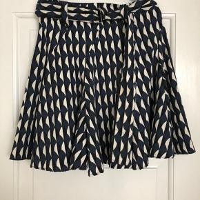 Mønstret nederdel i A-snit. Bindebånd medfølger.  Str.: s/m Brugt få gange.  Mønstret nederdel i A-snit. Bindebånd medfølger.  Str.: s/m Brugt få gange.  NB. Er gået op i syningen ved lynlåsen, pga. lidt søm. Se foto.