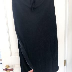 Flot nederdel i mat sort look, har slids i siderne