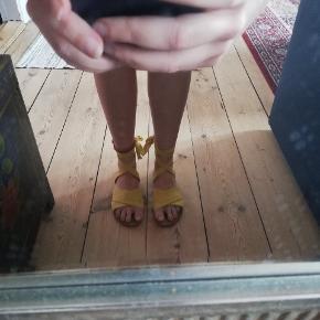 Fine, gule, binde sandaler, brugt enkelte gange. Har lidt slid på snuden. Wide fit.