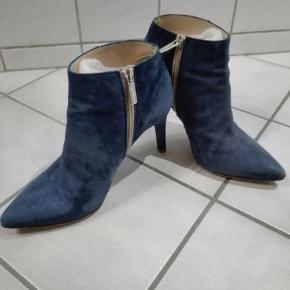 Flotte støvletter, blå ruskind. Lille hak på den ene hæl. Ellers flot i skindet.