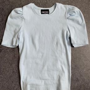 Pufærmet t-shirt fra pieces i en flot blå farve, pastel agtig   Sælges fordi jeg ikke kan lide den og har mistet kvitteringen.. købte den i en pieces butik for en uge siden