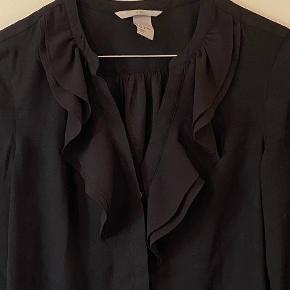 Sort bluse fra h&m med knapper og flæser foran.