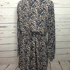 This animal print dress has a button-down neckline and a hidden drawstring to emphasize your waist.  100% viscose.  Machine wash warm.