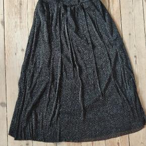 Højtaljet glimmer nederdel. Går til et godt stykke under knæene