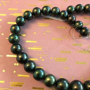 Flot grønlig spyfarvet perlekæde i forløb uden lås. Mindste perle måler 10,5 mm og den største 15 mm. med prismærke på.