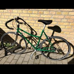 """Fed og velholdt grøn vintage pige-racer sælges. Cyklen har stået i garagen de sidste fire år, og har ikke været brugt i den periode. Den er oprindelig fra start 80'erne, og har naturligvis lidt kosmetiske skrammer og rust hist og her – rust primært på forgaflen. Kæde og andre dele er løbende smurt og vedligeholdt efter bedste evne. Cyklen kører fint, men i og med den har stået stille i nogle år, bør den lige """"spændes efter"""", justeres og smørres, af en med forstand på dette.  Stel: Stål – let, men robust.  Styr: SR Sakae Custom Modolo Anatomic Bend. Cykelbanditten har monteret nyt styrbånd i 2014, og har ligeledes flyttet bremsegrebene fra racerposition, til """"almindelig position"""" på styret. Det er mere behageligt til pendler/hverdagsbrug, da det giver en mindre aggressiv kørestilling.  Bremser: Shimano 105 serie for og bag.  Gear: Shimano 105 serie gearskiftere, for og bagskifter samt krank.  Hjul: Shimano 105 serie forhjul, nyere Shimano Tiagra baghjul (fra 2014).   Dækstørrelse: 25-622 (700x25c)   Billeder: https://photos.app.goo.gl/TcrHVn3aPPh5GErW6"""