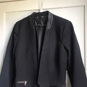 Sort blazer med lommer i siderne og læderkant i toppen. Kan ikke lukkes.  Jeg sender gerne - køber betaler fragt 📦 Bytter ikke.