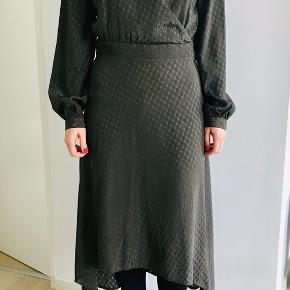 Fin kjole i blank kvalitet med jaquard mønster. Kjole har viscose foer. Slå-om effekt på overdel med lille trykknap. Kjolen er længere bag. Ærme har lille guldknap