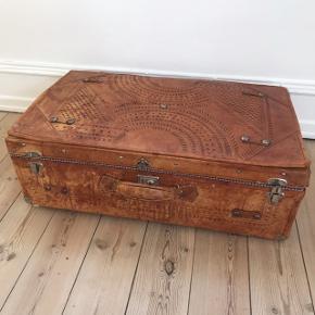 Gammel og fin kuffert til dekoration eller opbevaring. Ydermateriale er læder med fine mønstre på, inderst er der ternet stof. Er slidt og kan ikke lukkes ordentligt, men har har fin patina. Vi brugte den til legetøjskuffert på børneværelset.  Mål:  H: 25 cm  B: 75 cm  D: 45 cm