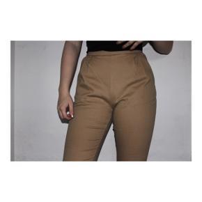 Sandfarvede bukser fra NA-KD i størrelse 36.