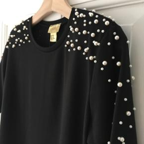 Sort T-shirt fra H&M med perler på skuldrene. Str. 40Skulderpuder kan tages af, da de er knappet på indvendigt. Aldrig brugt! Ny pris 199,-