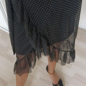 Brugt 2 gange.  Smuk chiffon nederdel med eleastik og binde bånd.  Med kort under lag inden under  Sort med karry/ guld farvet små prikker  Cm 80 Super flot