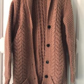 3/4 lang lækker strikcardigan med lommer foran. Materiale: 100% uld Farve: Nude med brunmelerede knapper.