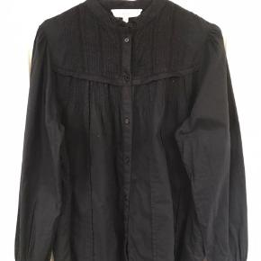 Sort bomuldsskjorte med fine detaljer over bryst, ryg og ved manchetterne.