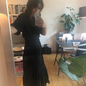 Sort kjole med diskret leopard print, der skinner lidt.