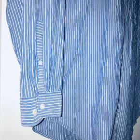 Flot blå/ hvid stribet bomulds skjorte. Den er købt oversize så kan bruges fra en 38-42, som løs eller normalt fit.   Brugt 3 gange.