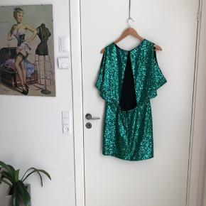 Festlig palliet kjole i en skøn grøn farve. Den har en dyb udskæring i ryggen og sidder stramt henover numsen og løst henover overkroppen. Man kan nemt bære kjolen uden bh - det kan ikke ses. Pasformen er helt igennem perfekt.  Den er lårkort og stram på rumpen så den bliver hvor den skal være.