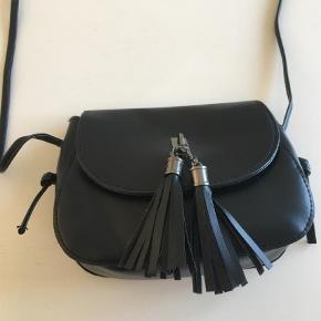 Varetype: Crossbody Størrelse: Længde 18 cm x højde 14 cm Farve: Sort Oprindelig købspris: 125 kr.  Sød lille sort taske. Ikke rigtig skind.  Aldrig brugt. Et rum i tasken med lynlås.