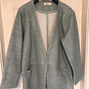 Jakke  i 56% polyester, 33% polyacryl og 11% uld. Lukkes med 1 knap. Lommer foran. Brystvidde: 68 cm. X X 2. Længde: 88 cm.