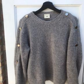 Mega flot sweater fra Heartmade sælges.  Modellen hedder Kelso i farven Taupe og har smukke guldknapper ned langs ærmerne. De kan både åbnes eller holdes lukket. (Se kommentarfelt) Sweateren er udsolgt overalt.  Den er kun brugt lidt.  Materiale: 40% Mercerized Super Wool 31% Polyamide 29% Kid Mohair  Str xs men oversize så passer xs-m Nypris 2200kr Sælges for 700kr  Skriv endelig for flere billeder!