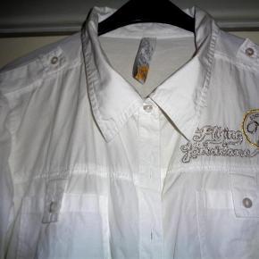 Varetype: Skjorte Farve: Hvid Prisen angivet er inklusiv forsendelse.  Lækker hvid skjorte m.2 brystlommer og påskrift i sølv og guld.  Brystmål 2 x 60 cm  Længde fra skulder og ned 65 cm    100% bomuld