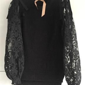 Brand: No21 Varetype: Sweater Farve: Sort Oprindelig købspris: 4000 kr.  Sort smuk sweater med blondeærmer. Der har været et lille hul bagpå, som er syet.  Bemærk min er sort!  Bank el mobilpay ellers TS gebyr oveni.
